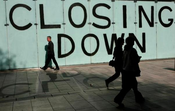 Shoppers walk past a closing down sign in a shop window in Cardiff, Wales